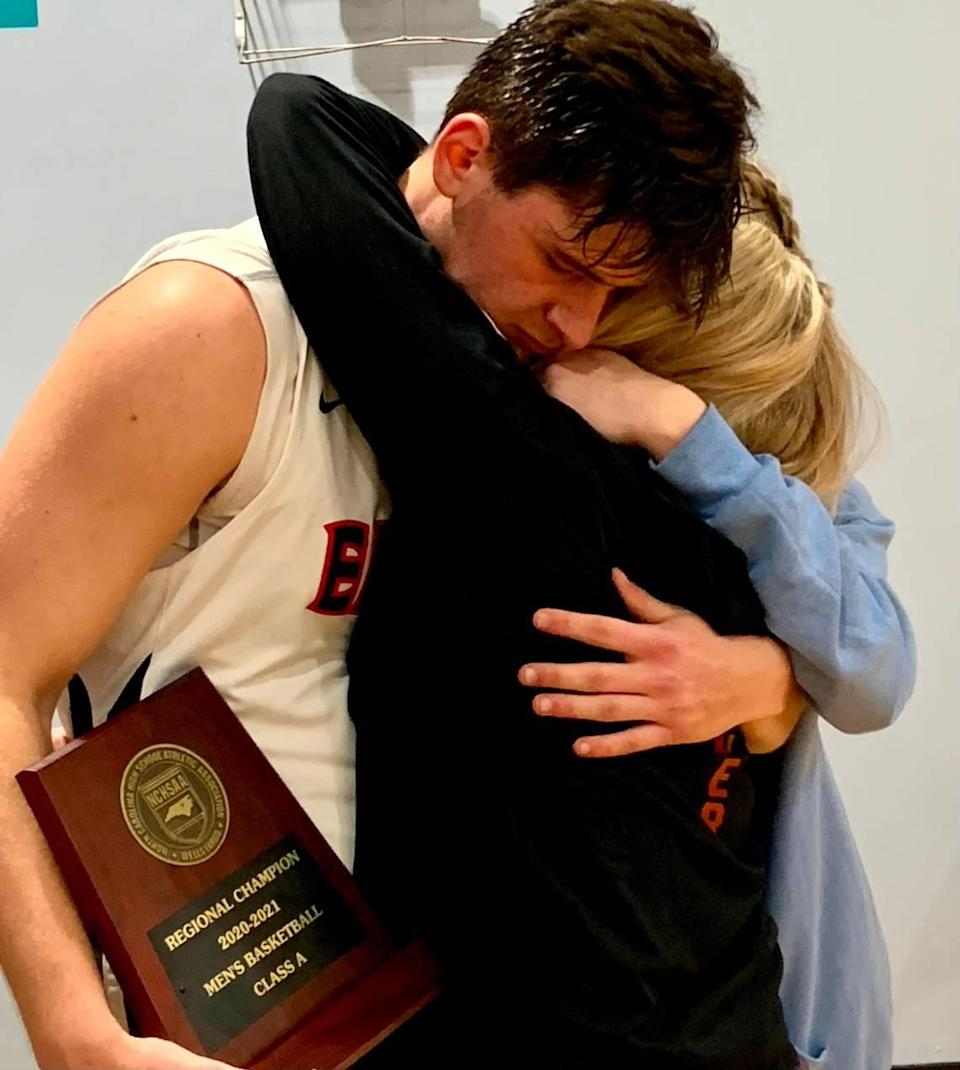 Carter Seitz (in uniform) hugs his mother Liz Seitz and his sister, Peyton Seitz, after Lincoln Charter won the 1A Western Regional Final over Mount Airy on Tuesday. Lincoln Charter advanced to the state final Saturday against Wilson Prep with the victory.
