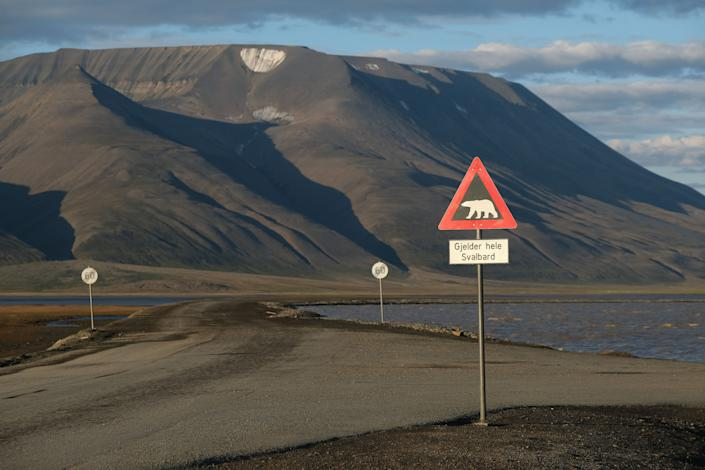 Mountains nearly devoid of snow stand behind a road and a polar bear warning sign during a summer heatwave on Svalbard archipelago on July 29 near Longyearbyen, Norway. (Photo: Sean Gallup via Getty Images)