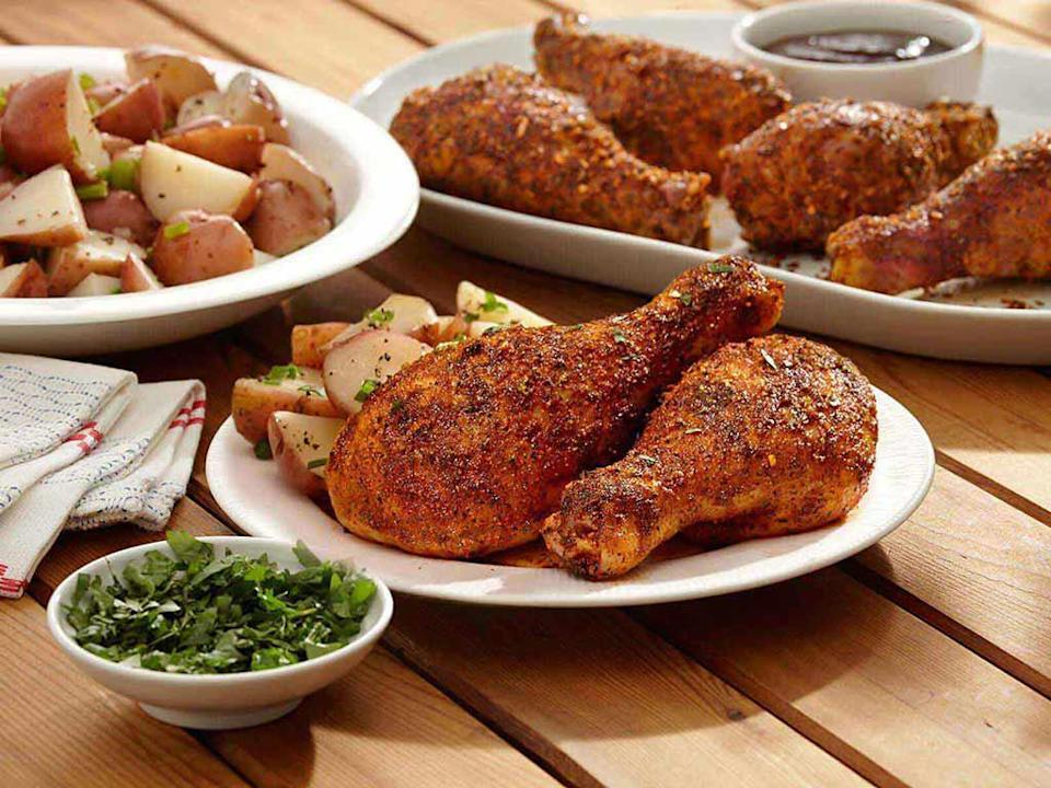 """<p>To make these drumsticks, you'll need lime, garlic and a seasoning rub —<a href=""""https://www.thedailymeal.com/recipes/dinosaur-bar-b-ques-spice-rub-recipe-recipe?referrer=yahoo&category=beauty_food&include_utm=1&utm_medium=referral&utm_source=yahoo&utm_campaign=feed"""" rel=""""nofollow noopener"""" target=""""_blank"""" data-ylk=""""slk:like this Dinosaur Bar-B-Que spice rub"""" class=""""link rapid-noclick-resp""""> like this Dinosaur Bar-B-Que spice rub</a> — to accomplish a zesty taste. After frying, top the chicken with fresh, chopped cilantro and pair with your sauce of choice. </p> <p><a href=""""https://www.thedailymeal.com/best-recipes/barbecue-chicken-drumsticks-easy?referrer=yahoo&category=beauty_food&include_utm=1&utm_medium=referral&utm_source=yahoo&utm_campaign=feed"""" rel=""""nofollow noopener"""" target=""""_blank"""" data-ylk=""""slk:For the Zesty BBQ Drumsticks recipe, click here."""" class=""""link rapid-noclick-resp"""">For the Zesty BBQ Drumsticks recipe, click here.</a></p>"""