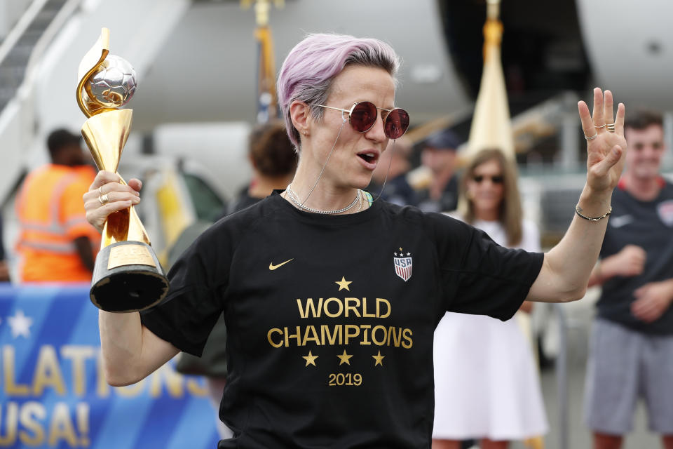Megan Rapinoe holds the Women's World Cup trophy after she and other members of the U.S. women's national soccer team, winners of a fourth Women's World Cup, celebrated after arriving at Newark Liberty International Airport, Monday, July 8, 2019, in Newark, N.J. (AP Photo/Kathy Willens)