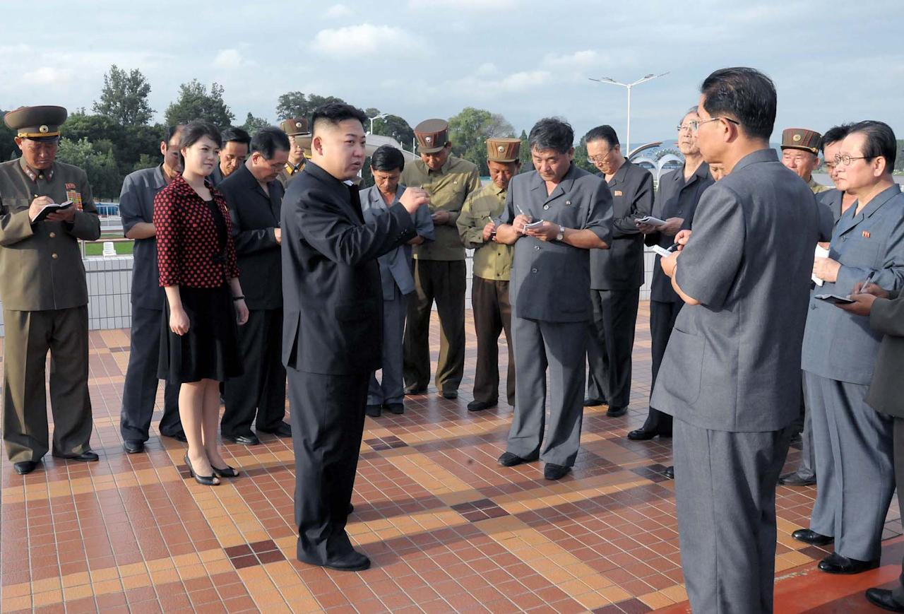 """In this image released by by the Korean Central News Agency (KCNA) and distributed in Tokyo by the Korea News Service on Wednesday July 25, 2012 North Korean leader Kim Jong-Un, centre, Ri Sol Ju, centre left. visit the Rungna People's Pleasure Ground, which is nearing completion, in this undated picture North Korea's new, young leader Kim Jong Un is married, state TV reported Wednesday for the first time in a brief and otherwise routine announcement that ends weeks of speculation about a beautiful woman who has accompanied him to recent public events. Kim toured an amusement park with his """"wife, comrade Ri Sol Ju"""" on Tuesday, while a crowd cheered for the leader, the news anchor said without giving any more details about Ri, including how long they had been married. (AP Photo/KCNA KNS) JAPAN OUT UNTIL 14 DAYS AFTER THE DAY OF TRANSMISSION"""