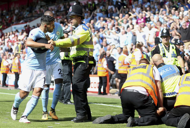 "<a class=""link rapid-noclick-resp"" href=""/soccer/teams/manchester-city/"" data-ylk=""slk:Manchester City"">Manchester City</a>'s Sergio Aguero is held back by police after <a class=""link rapid-noclick-resp"" href=""/soccer/players/raheem-sterling/"" data-ylk=""slk:Raheem Sterling"">Raheem Sterling</a>'s winner and the ensuing celebrations. (Steve Paston/PA via AP)"
