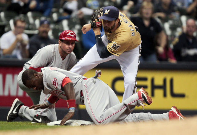 Cincinnati Reds' Brandon Phillips, bottom, is tagged out at third by Milwaukee Brewers' Jeff Bianchi, top right, during the fifth inning of a baseball game on Sunday, Sept. 15, 2013, in Milwaukee. (AP Photo/Andy Manis)