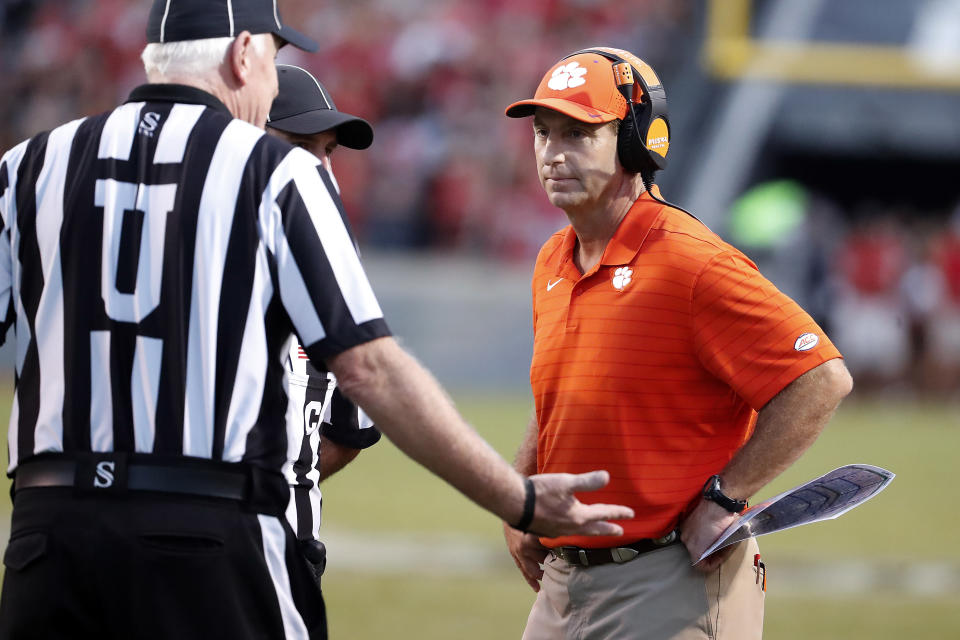 Clemson head coach Dabo Swinney, right, speaks with officials during the second half of an NCAA college football game against North Carolina State in Raleigh, N.C., Saturday, Sept. 25, 2021. (AP Photo/Karl B DeBlaker)