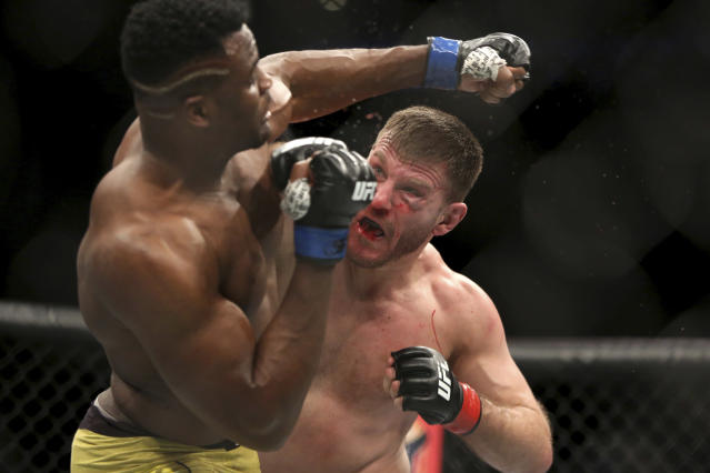 Stipe Miocic, right, lands a right hand against Francis Ngannou during a heavyweight championship mixed martial arts bout at UFC 220, early Sunday, Jan. 21, 2018, in Boston. Miocic retained his title via unanimous decision. (AP Photo/Gregory Payan)