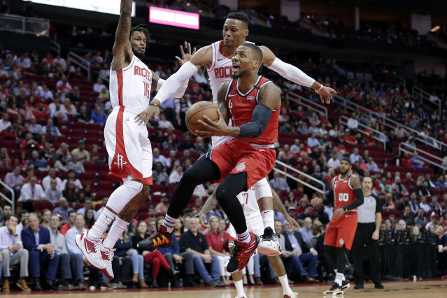 Portland Trail Blazers guard Damian Lillard, middle, puts up a shot in front of Houston Rockets guard Ben McLemore (16) and guard Russell Westbrook, back, as forward Carmelo Anthony (00) looks on during the first half of an NBA basketball game Wednesday, Jan. 15, 2020, in Houston. (AP Photo/Michael Wyke)