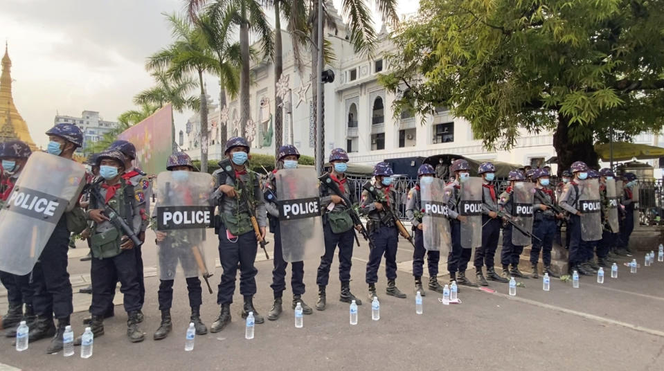 In this image from video, armed Myanmar police blocking a road to withhold protesters outside Yangon City Hall, in Yangon, Saturday Feb. 6, 2021. Myanmar's new military authorities appear to have cut most access to the Internet as they face a rising tide of protest over their coup that toppled Aung San Suu Kyi's elected civilian government. (AP Photo)