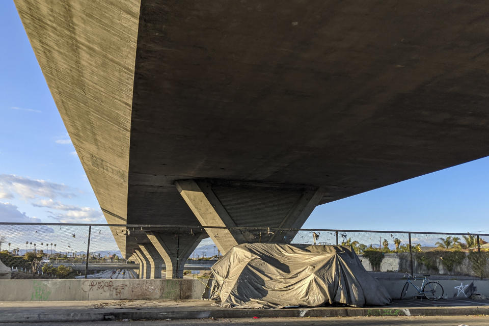 Homeless people camp under Interstate 110 in downtown Los Angeles on Friday, March 27, 2020. On Friday, California Gov. Gavin Newsom and Los Angeles Mayor Eric Garcetti said the surge in COVID-19 that health officials warned about will worsen. (AP Photo/Damian Dovarganes)