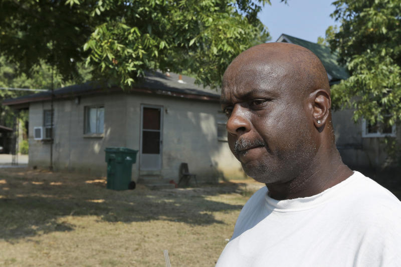 Dwayne Grant, former neighbor of 107-year-old Monroe Isadore, is interviewed Monday, Sept. 9, 2013, near Isadore's former residence in Pine Bluff, Ark. Police halted a standoff at another address Saturday, Sept. 7, when they shot Isadore who they say opened fire at them. (AP Photo/Danny Johnston)