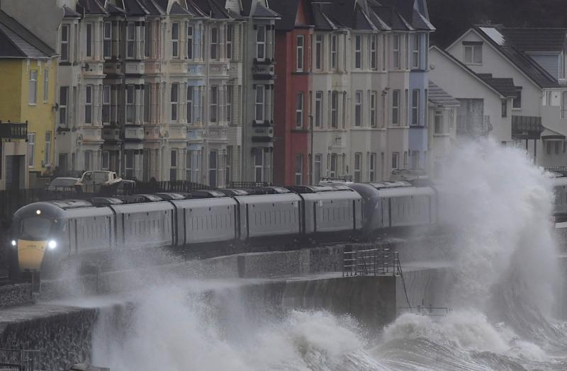 Large waves hit the sea wall with Storm Brendan bringing high winds and heavy rain, as a train passes through Dawlish, southwest Britain, January 14, 2020. REUTERS/Toby Melville