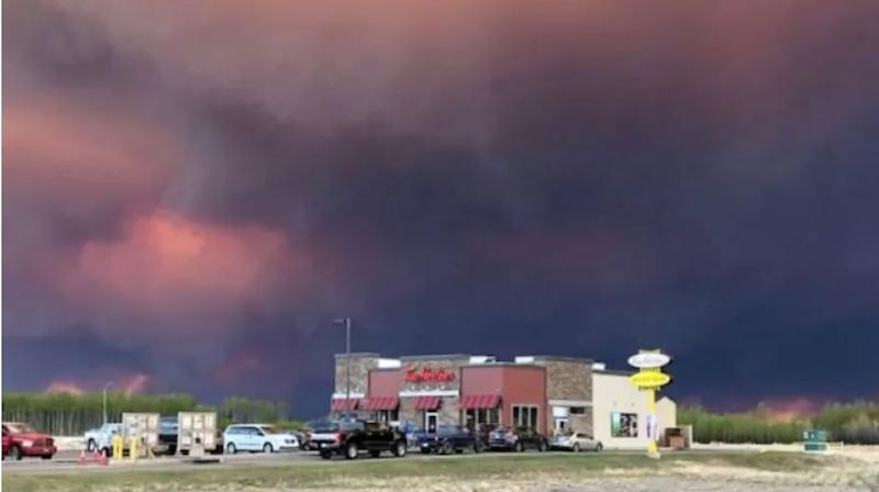 Smoke from a wildfire 25 kilometres southwest of High Level, Alta. hovered over the town May 19, 2019. Alberta Wildfire says the community is not at risk. (Deb Stecyk/CBC News)