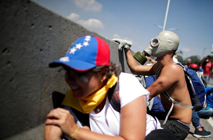 """An opposition demonstrator peers out from behind a concrete divider as others take over on a street near the Generalisimo Francisco de Miranda Airbase """"La Carlota"""" in Caracas, Venezuela April 30, 2019. (Photo: Ueslei Marcelino/Reuters)"""