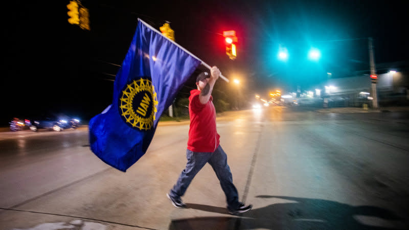 Davison resident Jeff Elkins, 37 and a GM employee who works on the line, walks across Van Slyke Road proudly waving a UAW flag as General Motors employees leave the Flint Assembly Plant at midnight as part of the national strike on Monday, Sept. 16, 2019 in Flint, Michigan. (Jake May/The Flint Journal via AP)
