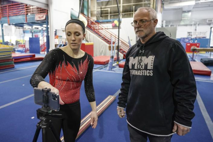 Former world champion and Olympic silver medalist Chellsie Memmel works out with her father and coach Andy Memmel Thursday, Feb. 18, 2021, in New Berlin, Wisc. Memmel, 32, is attempting a comeback. (AP Photo/Morry Gash)