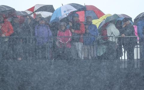 Spectators shelter from a severe rain shower during the first round of the 148th Open Championship held on the Dunluce Link - Credit: DAVID CANNON
