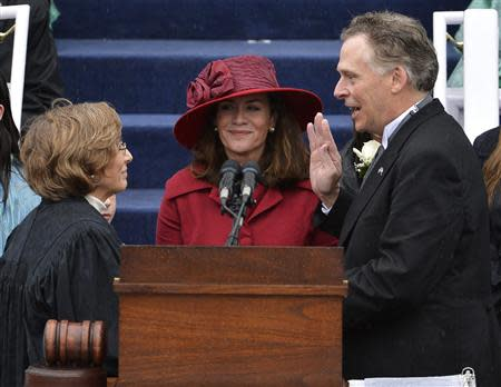 Terry McAuliffe (R) is sworn in as Virginia's governor by Supreme Court Chief Justice Cynthia Kinser (L) as McAuliffe's wife Dorothy witnesses, in Richmond, Virginia, January 11, 2014. REUTERS/Mike Theiler