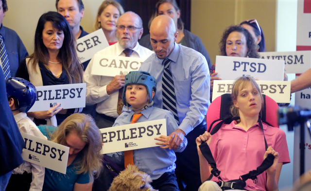 Davis Cromar holds his son Holden, 10, who suffers from epilepsy, while standing with other patients, caregivers and supporters during a Utah Patients Coalition news conference in 2017. (Photo: Rick Bowmer/AP)