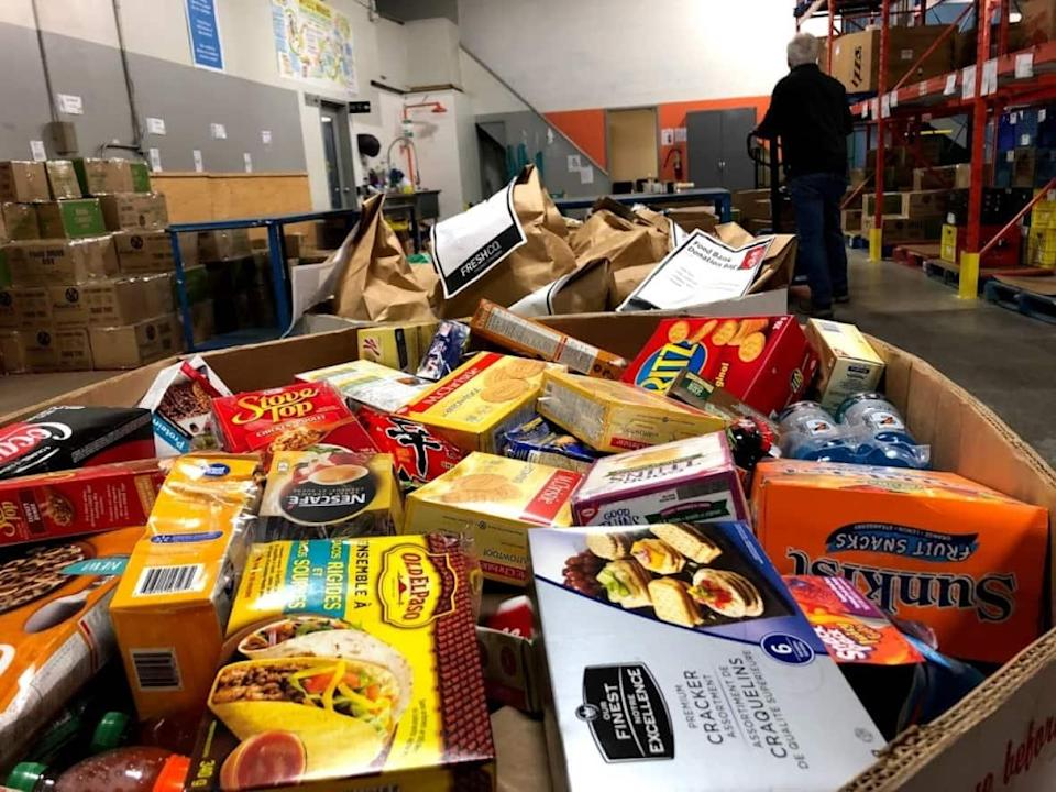 Donations from the public, like those made at grocery stores or company food drives, sit in large cardboard bins at The Food Bank of Waterloo Region.  Feed Ontario, which works with provincial food banks, has launched a new tool called Hunger In My Riding to inform people about the need for food in their community. (Kate Bueckert/CBC - image credit)