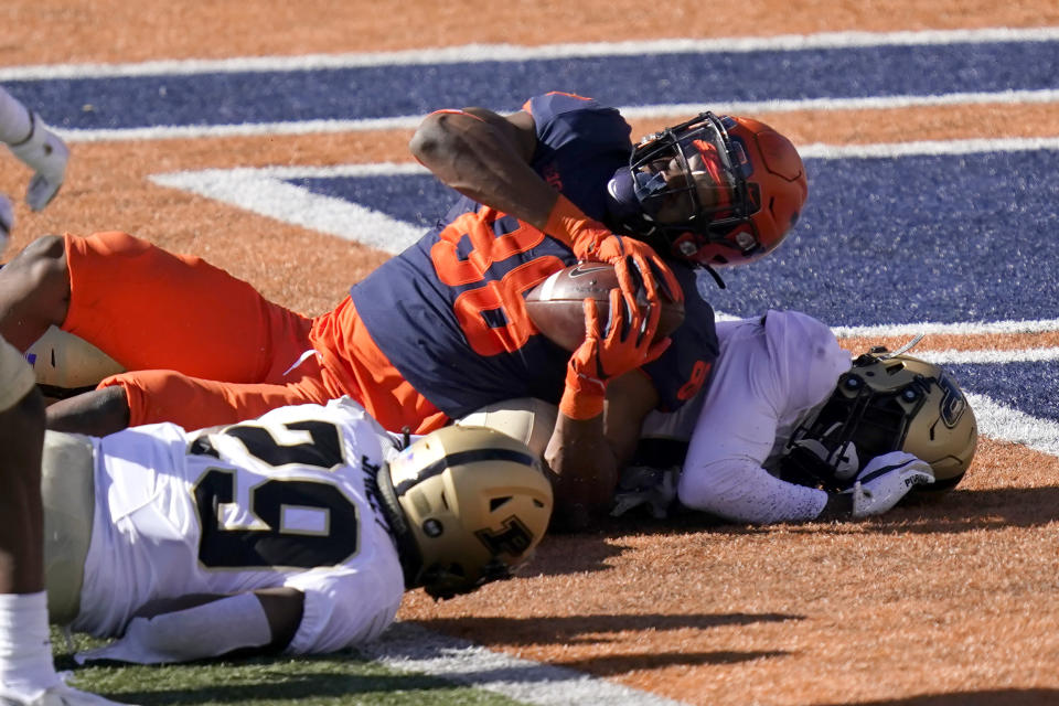 Illinois tight end Daniel Imatorbhebhe (88) falls into the end zone for a touchdown as Purdue cornerback Simeon Smiley, left, and DJ Johnson defend during the second half of an NCAA college football game Saturday, Oct. 31, 2020, in Champaign, Ill. (AP Photo/Charles Rex Arbogast)