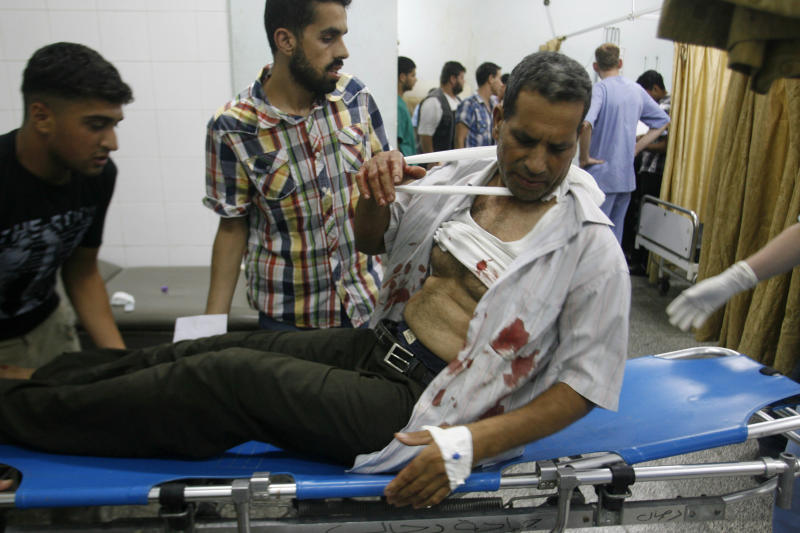 Palestinians bring a wounded man to the treatment room of Al Najar Hospital following an Israeli airstrike in Rafah, southern Gaza Strip, Monday, June 18, 2012. Palestinian medics said five Palestinians were wounded during the airstrike on a metal workshop. The Israeli military said a weapon manufacturing facility was targeted during the airstrike. (AP Photo/Eyad Baba)