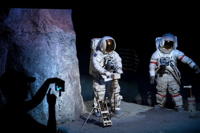 A woman takes a photo of a lunar scene at the Space Center Houston in Houston, Texas, July 11, 2017.