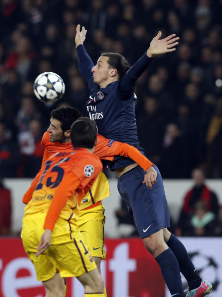 Paris Saint Germain's Zlatan Ibrahimovic tries to head the ball with FC Barcelona's players during their Champions League quarterfinal soccer match in Paris,Tuesday, April 2, 2013. (AP Photo/Christophe Ena)