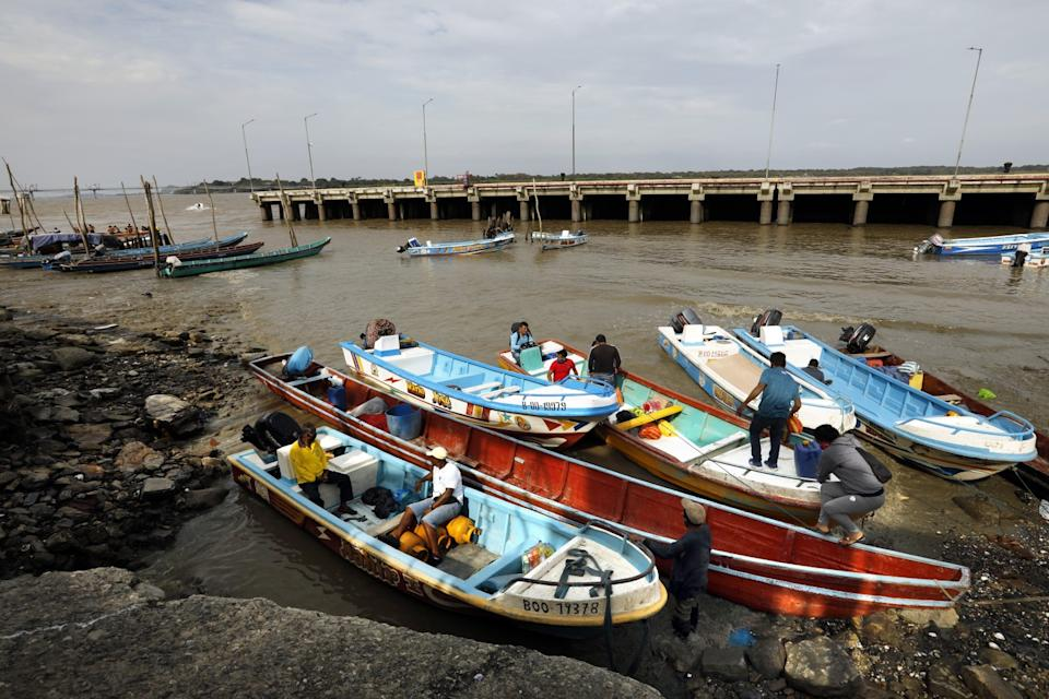 Workers unload fishing boats on the Rio Guayas in Guayaquil, Ecuador.