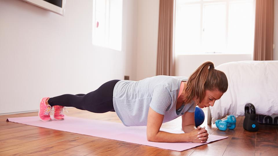 Woman Doing Fitness Exercises On Mat In Bedroom.