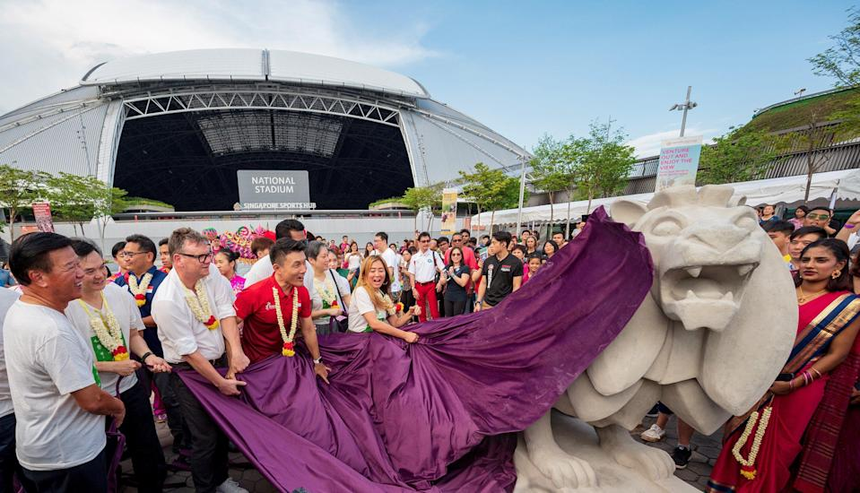 Senior Parliamentary Secretary for the Ministry of Culture, Community and Youth Baey Yam Keng (in red shirt) unveiling one of two Merdeka Lions in front of the National Stadium during the launch of the Kallang sports, arts and heritage trail. (PHOTO: Singapore Sports Hub)