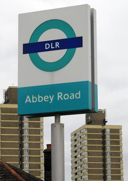 "The sign for east London's Abbey Road Station is seen against the backdrop of apartment buildings on Friday, Nov. 10, 2012. Abbey Road Station is more than nine miles from the striped crosswalk made famous by the Beatles album ""Abbey Road,"" but this drab transit hub keeps drawing confused fans of the Fab Four into unwanted jaunts through a gritty, industrial area of east London. (AP Photo/Raphael Satter)"