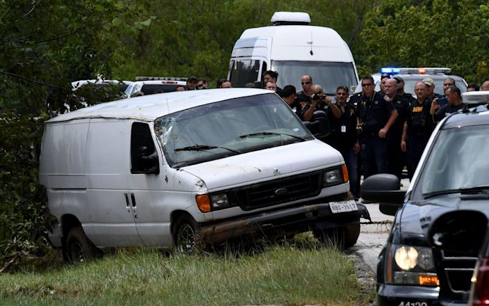 Police investigators watch as the van containing the six members of the the Saldivar family who died is towed to the road after they crashed their van into Greens Bayou as they tried to flee Hurricane Harvey during heavy flooding in Houston, Texas on August 30, 2017 - AFP