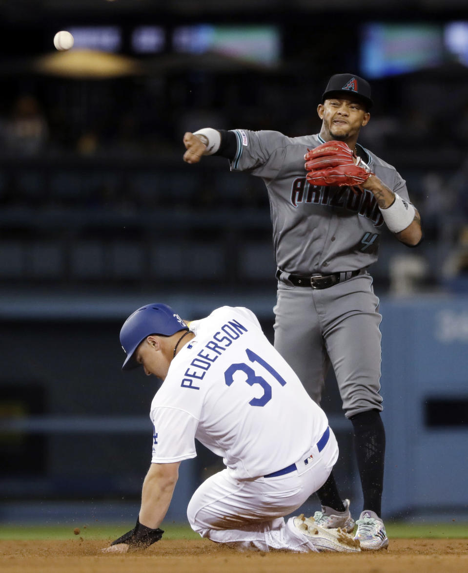 Arizona Diamondbacks shortstop Ketel Marte, top, throws to first after forcing out Los Angeles Dodgers' Joc Pederson (31) at second base on a ground ball by Russell Martin, who was safe at first during the sixth inning of a baseball game Friday, March 29, 2019, in Los Angeles. (AP Photo/Marcio Jose Sanchez)