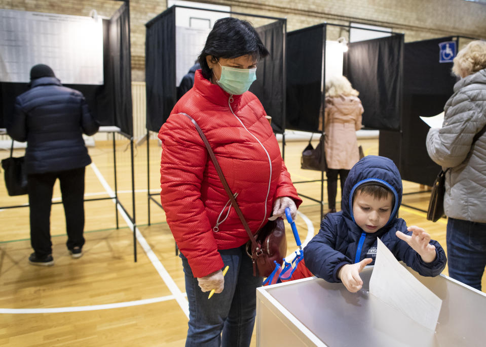 A woman with a child casts her ballot at a polling station during parliamentary elections in Vilnius, Lithuania, Sunday, Oct. 11, 2020. Polls opened Sunday for the first round of national election in Lithuania, where voters will renew the 141-seat parliament and the ruling four-party coalition is widely expected to face a stiff challenge from the opposition to remain in office. (AP Photo/Mindaugas Kulbis)