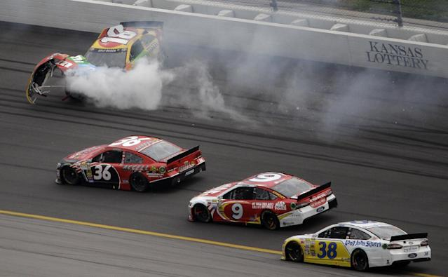 Drivers J.J. Yeley (36), Marcos Ambrose (9) and David Gilliland (38) pass by Kyle Busch's wrecked car during a NASCAR Sprint Cup series auto race at Kansas Speedway in Kansas City, Kan., Sunday, Oct. 6, 2013. (AP Photo/Charlie Riedel)