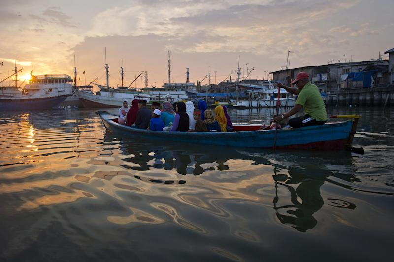 Indonesian Muslim devotees arrive on a boat to attend the morning prayer to celebrate the Eid al-Fitr festival at the historic Sunda Kelapa port district of Jakarta on July 28, 2014 (AFP Photo/Romeo Gacad)