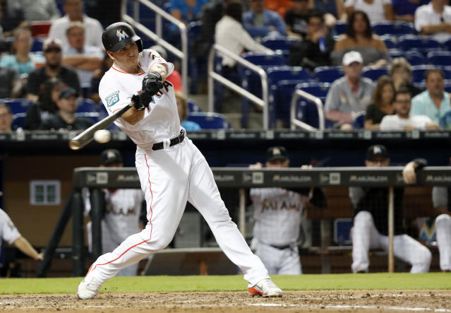 Miami Marlins' J.T. Realmuto gets a base hit scoring JT Riddle during the fifth inning of a baseball game against the Washington Nationals, Tuesday, Sept. 18, 2018, in Miami. (AP Photo/Wilfredo Lee)