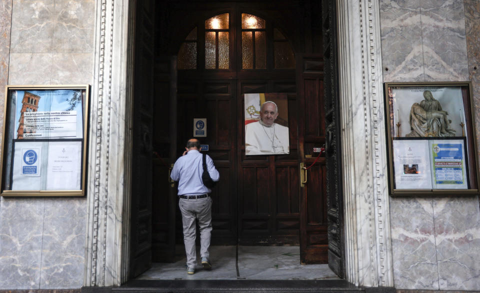 A man passes past a portrait of Pope Francis as he enters the Argentine church of Santa Maria Addolorata (Our Lady of Sorrows) in Rome, Sunday, July 4, 2021. Pope Francis was hospitalized in Rome on Sunday afternoon for scheduled surgery on his large intestine, the Vatican said. The news came just three hours after Francis had cheerfully greeted the public in St. Peter's Square and told them he will go to Hungary and Slovakia in September. (AP Photo/Riccardo De Luca)