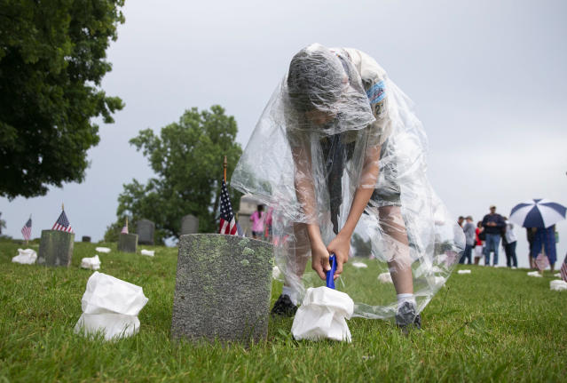 <p>Alex Kies, a Boy Scout with Troop 218, tries to light soggy luminaria following a thunderstorm, at the annual Fredericksburg National Cemetery Illumination in Fredericksburg, Va., Saturday, May 26, 2018. Boy Scouts from the Mattaponi and Aquia districts and Commonwealth Council Girl Scouts placed luminarias at more than 15,000 graves in the cemetery. (Photo: Mike Morones/The Free Lance-Star via AP) </p>