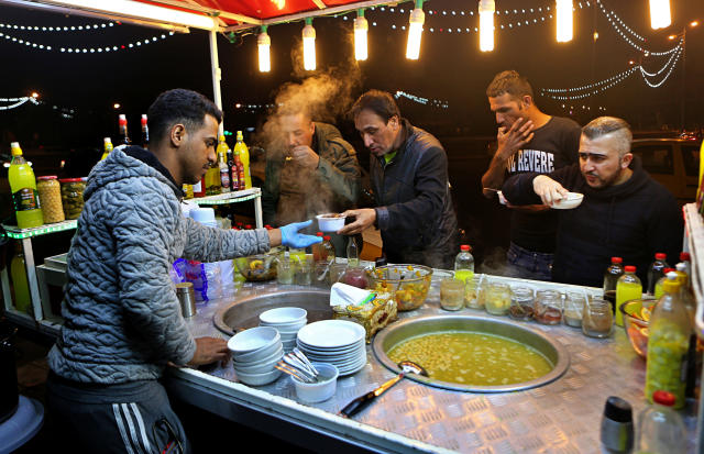 In this Feb. 13, 2019 photo, a chickpea soup vendor serves customers at a roadside stand, Tahrir Square, in Baghdad, Iraq. For the first time in years, Iraq is not at war. The defeat of the Islamic State group in late 2017 after a ruinous four-year conflict has given the population a moment of respite, and across the capital Baghdad there is a guarded sense of hope. (AP Photo/Khalid Mohammed)