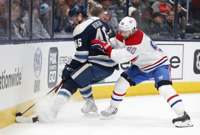 Columbus Blue Jackets' Dean Kukan, left, of Switzerland, tries to control the puck as Montreal Canadiens' Tomas Tatar, of Slovakia, defends during the first period of an NHL hockey game Tuesday, Nov. 19, 2019, in Columbus, Ohio. (AP Photo/Jay LaPrete)
