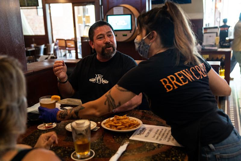 Sloane Sires of Long Beach, right, delivers a beer to Keith Gaxiola, center, of Santa Monica as people dine at the San Pedro Brewing Co. on Friday.