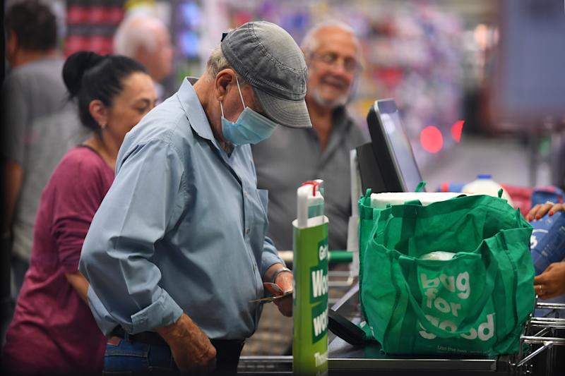 A man in Woolworths where staff have ceased packing items into used bags for customers. Source: AAP