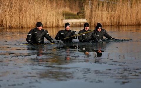 Four officers wadethrough the waist-deep water, using sticks to break the ice and search beneath the surface - Credit: SWNS