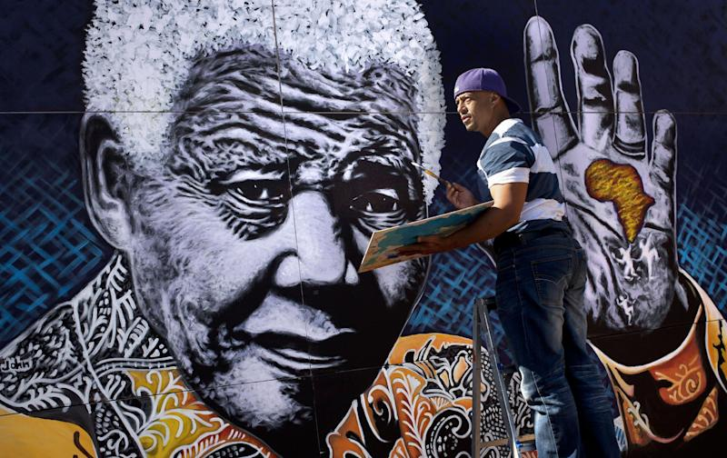 FILE - In this Monday, July 15, 2013 file photo, South African artist John Adams works on a giant acrylic-on-canvas painting of Nelson Mandela in the driveway of his house in a suburb of Johannesburg, South Africa. Many South African artists and graphic designers are celebrating Nelson Mandela's 95th birthday who remains hospitalized as hit condition improves Thursday July 18, 2013.(AP Photo/Ben Curtis, File)