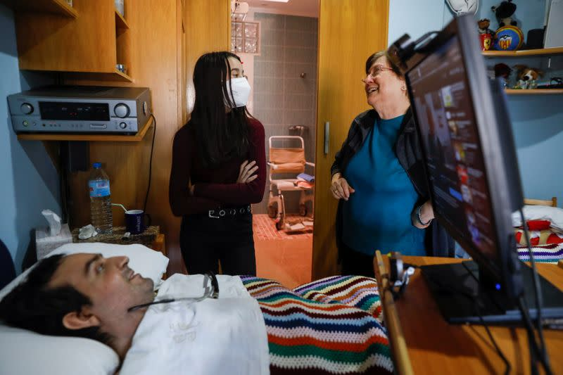 Rafael Botella, 35, tetraplegic since he was 19 after a car crash where his girlfriend died, chats with his mother Maria Luisa, 73, and his goddaugther Aitana, 12, at his home in Simat de la Valldigna