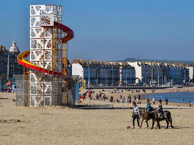 A bright idea: beachgoers in Dorset enjoy the balmy weather with suntanning and horseback rides