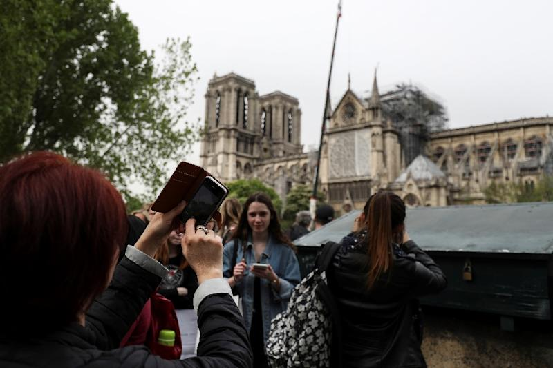 Tourists remain drawn to the historic monument, many pausing to snap pictures of its damaged roof (AFP Photo/KENZO TRIBOUILLARD)
