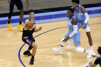 Phoenix Suns guard Devin Booker (1) gets the ball as Houston Rockets guard Victor Oladipo (7) and center Christian Wood (35) defend during the first half of an NBA basketball game Wednesday, Jan. 20, 2021, in Houston. (AP Photo/Michael Wyke)
