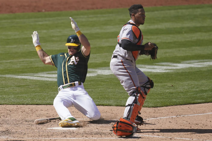 Oakland Athletics' Matt Chapman, left, scores next to Baltimore Orioles catcher Pedro Severino during the seventh inning of a baseball game in Oakland, Calif., Sunday, May 2, 2021. (AP Photo/Jeff Chiu)