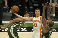 Atlanta Hawks' Bogdan Bogdanovic shoots between Milwaukee Bucks' P.J. Tucker and Giannis Antetokounmpo during the second half of Game 1 of the NBA Eastern Conference basketball finals game Wednesday, June 23, 2021, in Milwaukee. (AP Photo/Morry Gash)